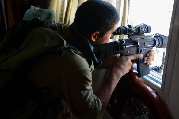 An Israeli paratrooper takes aim inside a Gazan building.  From the IDF flickr account.