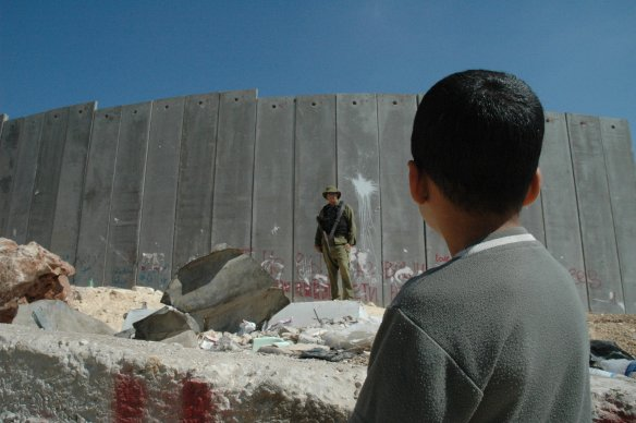 Boy_and_soldier_in_front_of_Israeli_wall